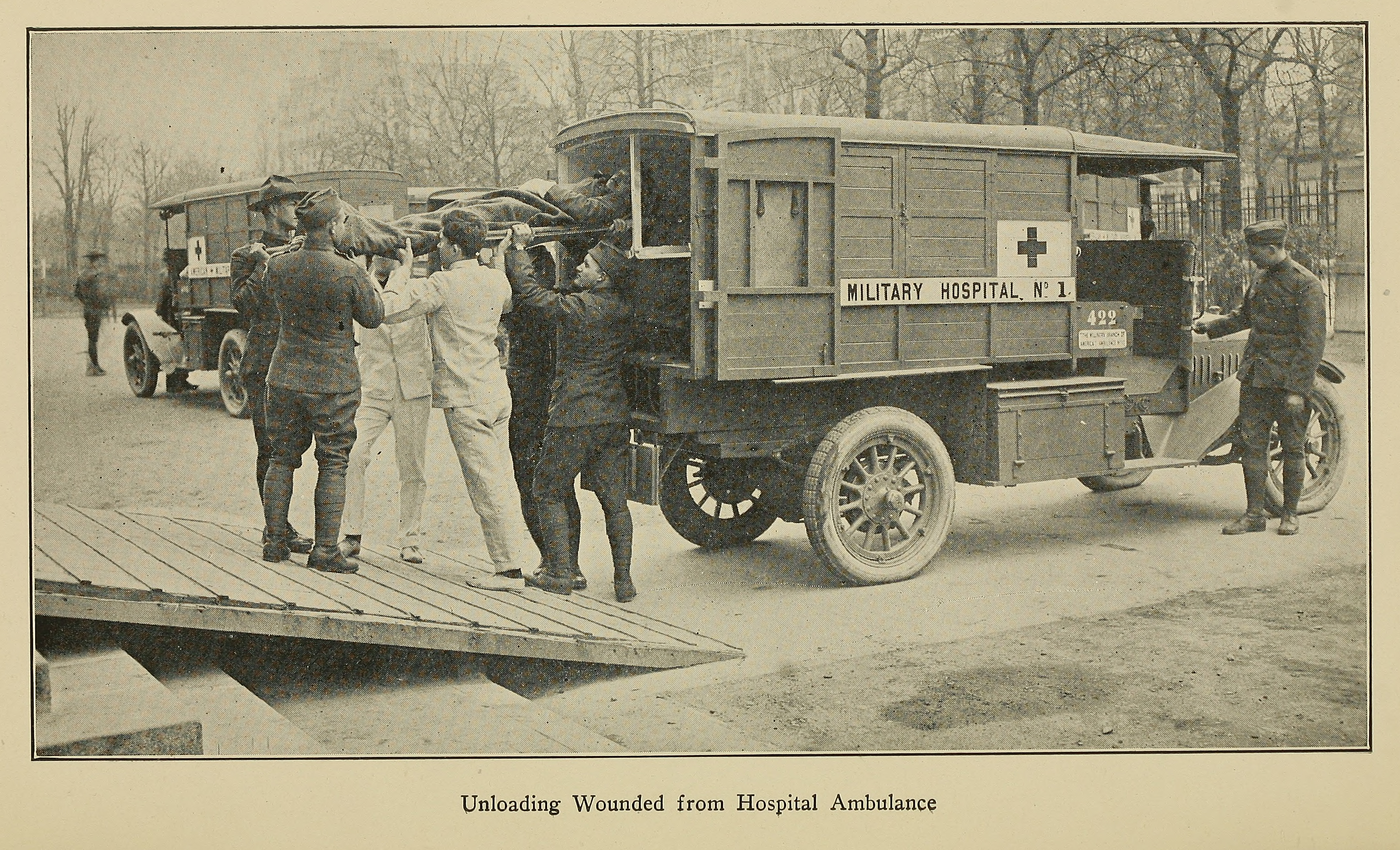 """Unloading Wounded from Hospital Ambulance."" Illustration from American Military Hospital No. 1, formerly American Ambulance Hospital of Paris (1918)."